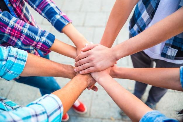 Studenten in het park slaan hun handen in elkaar als een echt team.