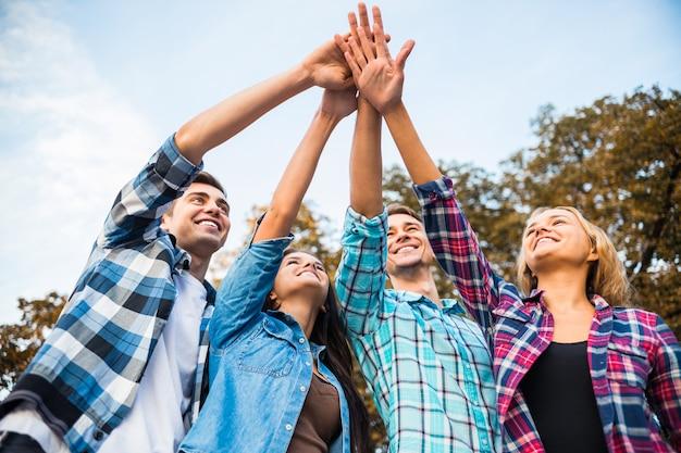 Studenten leggen hun handen samen als een echt team.