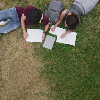Studenten liggen op gras met notitieboekjes studeren