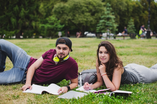 Studenten liggen op het gras met notitieblokken