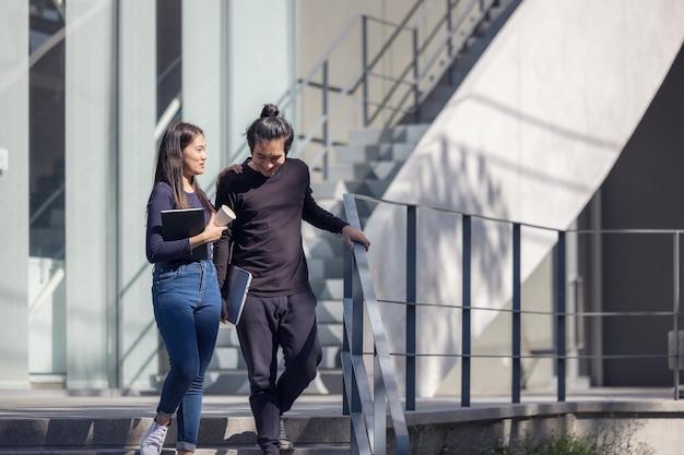 Studenten lopen de trappen op de campus, een stel loopt de grond in voor extra onderwijs.