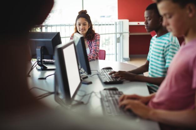 Studenten met behulp van computer in de klas