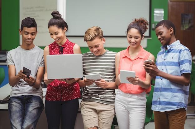 Studenten met behulp van laptop, mobiele telefoon, digitale tablet