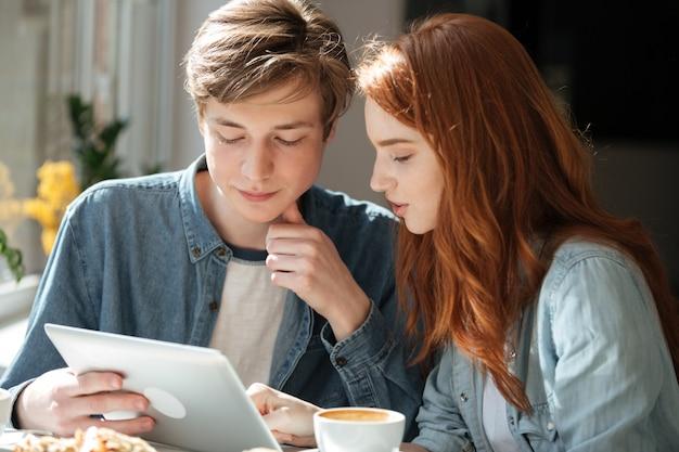 Studenten met behulp van tablet in café