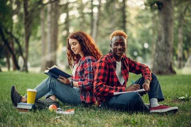 Studenten met boek zittend op het gras met hun rug naar elkaar toe