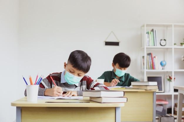 Studenten met een medisch masker studeren en doen opdrachten in de klas