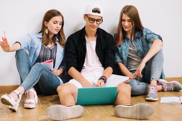 Studenten met gadget en notitieblokken koesteren