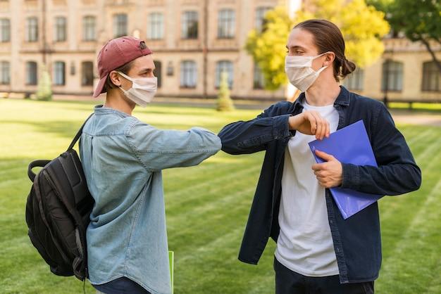 Studenten met gezichtsmaskers begroeten elkaar