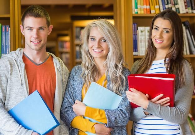 Studenten met mappen staande tegen boekenplank in de bibliotheek