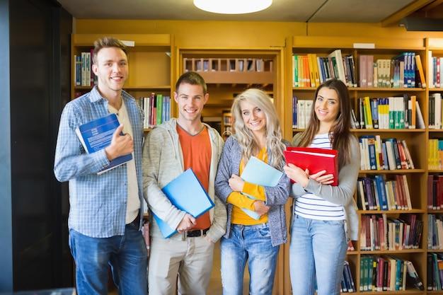 Studenten met mappen tegen boekenplank in bibliotheek