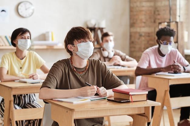 Studenten met maskers die op school studeren