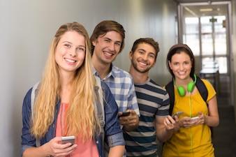 Studenten met mobiele telefoons op college gang