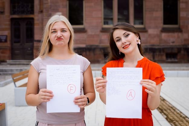 Studenten met testresultaten staan in de buurt van de universiteit