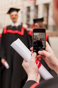 Studenten nemen foto's tijdens de diploma-uitreiking