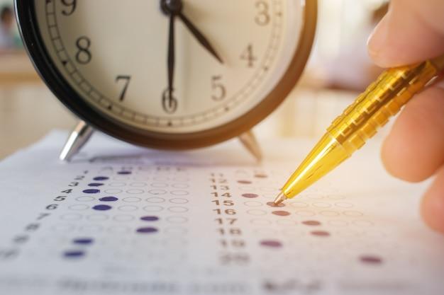 Studenten nemen optische vorm van gestandaardiseerde examens nabij wekker