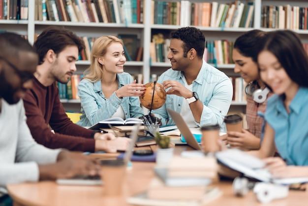 Studenten praten en lezen in de bibliotheek