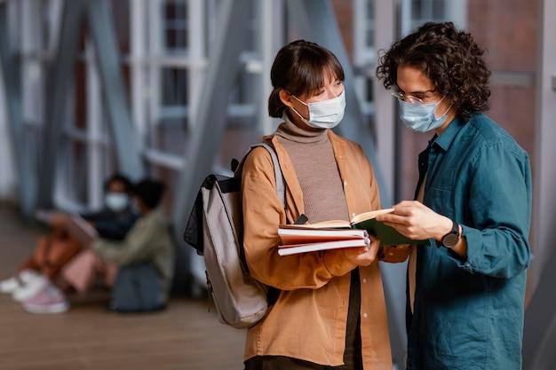 Studenten praten terwijl ze medische maskers dragen