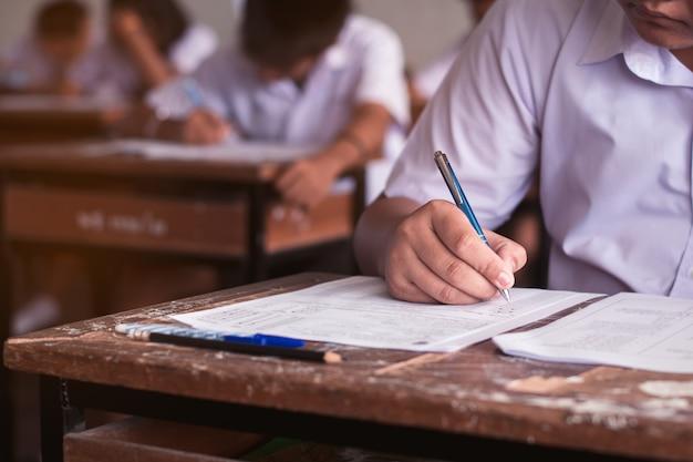 Studenten schrijven antwoord doen examen in de klas