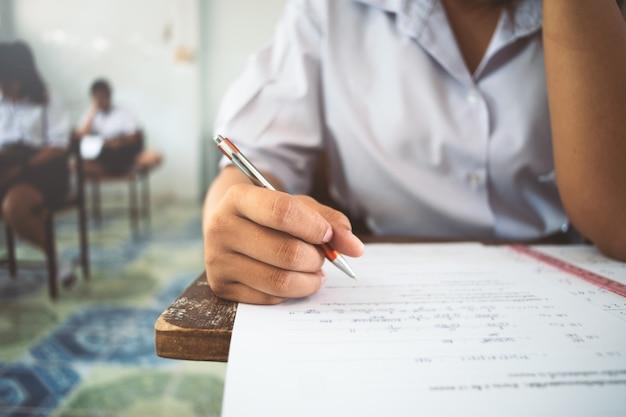 Studenten schrijven en lezen examen antwoorden bladen oefeningen in de klas van school met stress.