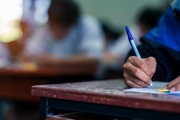 Studenten schrijven en lezen examenantwoordbladen oefeningen in de klas van school met stress