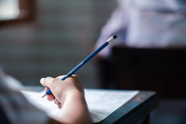 Studenten schrijven en lezen examenantwoordbladen oefeningen op school met stress