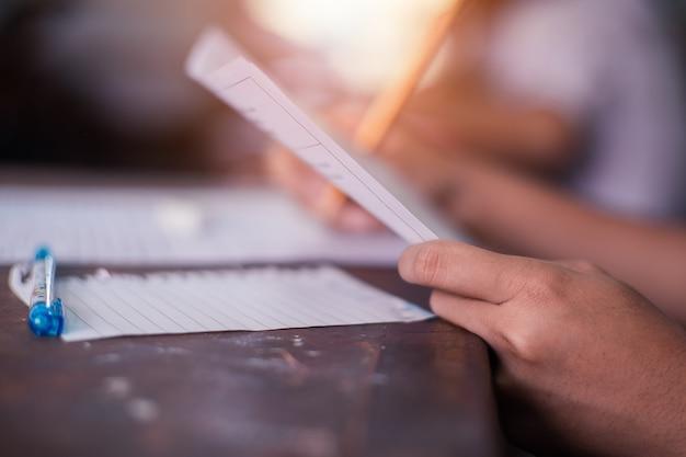 Studenten schrijven en lezen examenantwoordbladen op school met stress