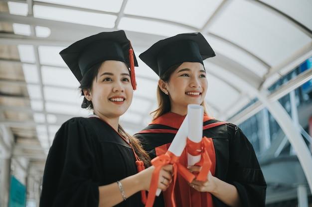 Studenten studeren af met diploma's en gouden prijsmunten Premium Foto