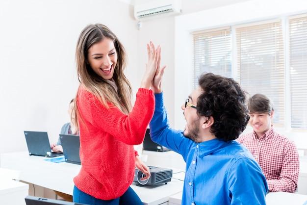 Studenten, vrouw en man, geven high five