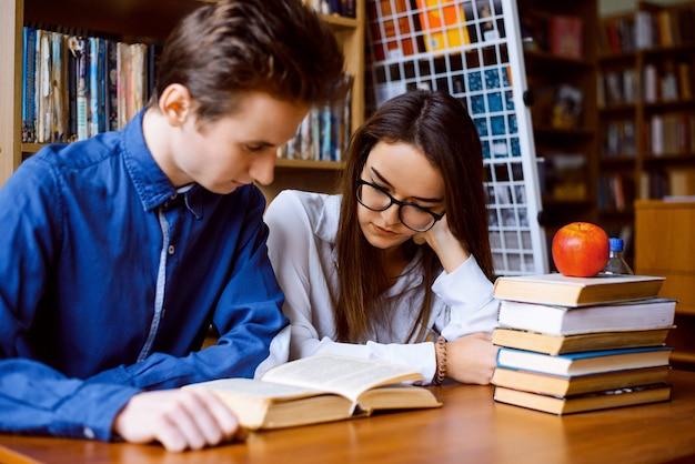 Studenten werken samen met veel boeken in de bibliotheek