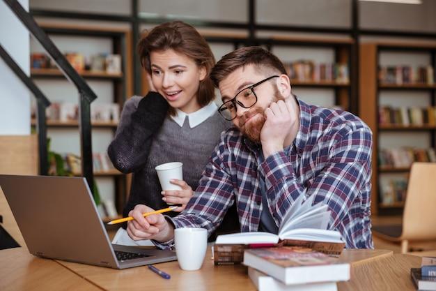 Studenten zitten aan de tafel met laptopcomputer in bibliotheek