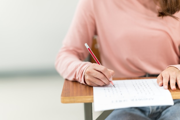 Studenten zitten voor examens aan de bureaus in de klas op de universiteit.