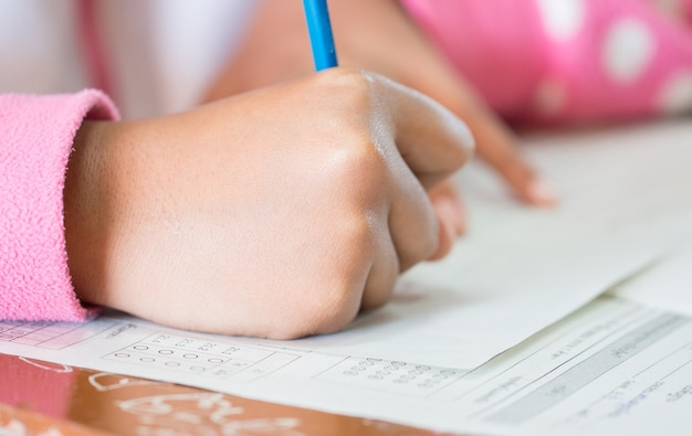 Studentenconcentratie die potloden in hand houden die testende examens multiple-choice quizzen doen