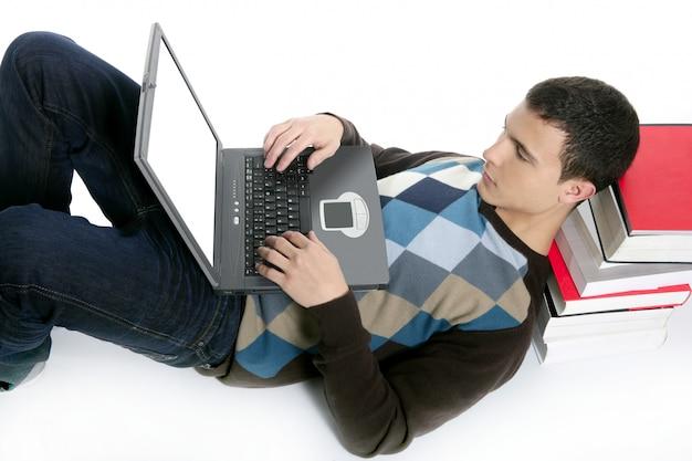 Studentenjongen die op vloer, boeken en computer liggen