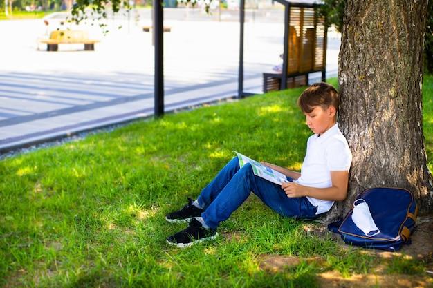 Studentenjongen doet huiswerk in het park tijdens covid 19 pandemie