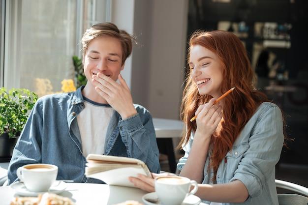 Studentenjongen en meisje die in koffie lachen