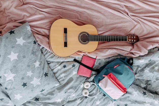 Studentenkamer na studie. gitaar, rugzak, koptelefoon en notitieboekje op het bed.