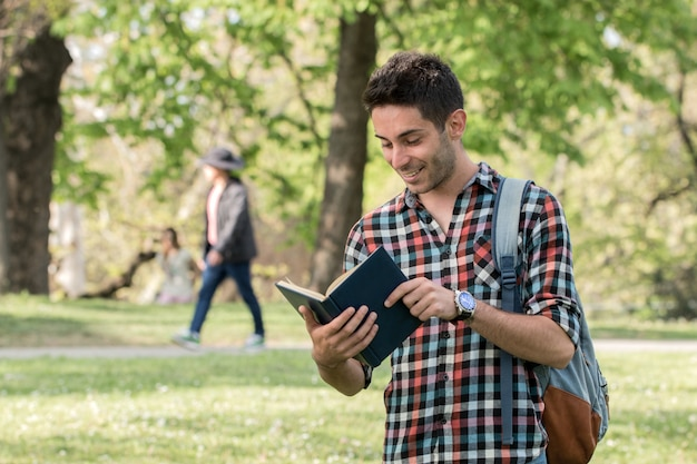 Studentenkerel die huiswerk in het park doen.