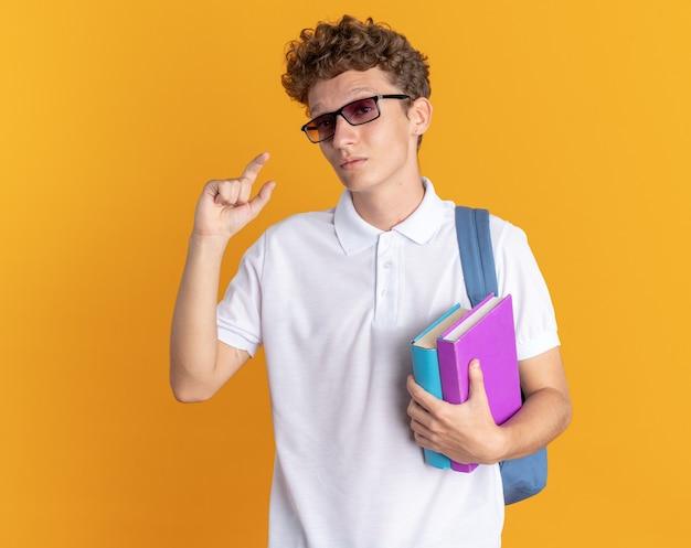 Studentenkerel in vrijetijdskleding met een bril met rugzak die boeken vasthoudt en naar een camera kijkt die een klein gebaar toont met vingers die over een oranje achtergrond staan