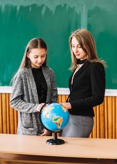 Studentenmeisje die aardrijkskunde met vrouwelijke leraar leren