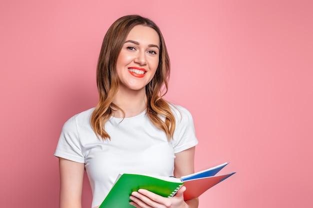 Studentenmeisje die een oefenboek, een notitieboekje en een glimlach houden die over roze achtergrond wordt geïsoleerd