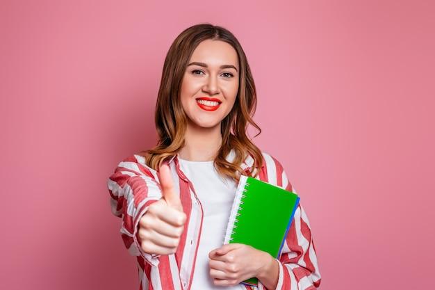 Studentenmeisje die een oefenboek houden en als gebaar met hand tonen die over roze achtergrond wordt geïsoleerd