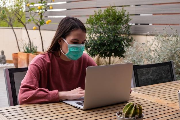 Studentenmeisje die gezichtsmasker dragen en laptop thuis buiten gebruiken