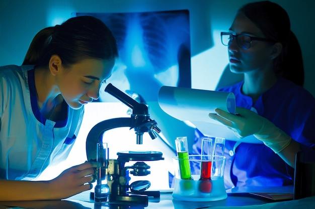 Studentenmeisje die in een microscoop, het concept van het wetenschapslaboratorium kijken.
