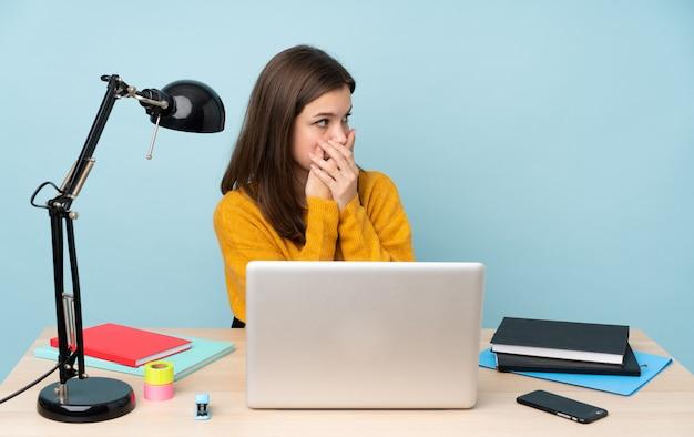 Studentenmeisje die in haar huis op blauwe muur bestuderen die mond behandelen en aan de kant kijken