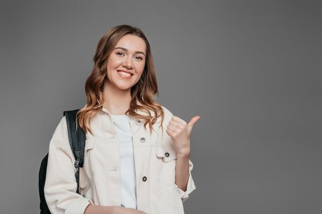 Studentenmeisje die met rugzak een vinger richten om ruimte te kopiëren over grijze muurachtergrond wordt geïsoleerd