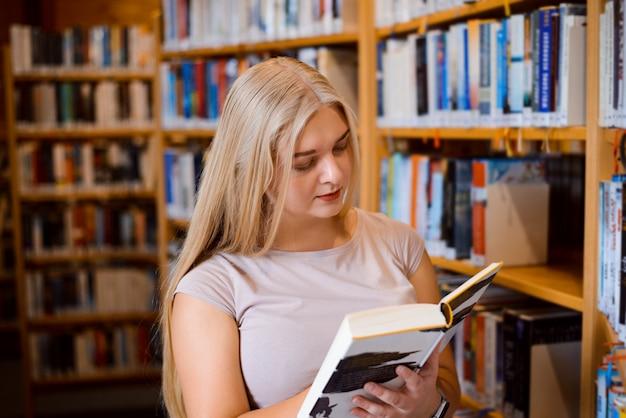 Studentenmeisje die noodzakelijke informatie zoeken bij bibliotheek