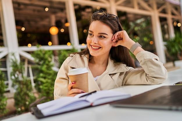 Studentenmeisje die online buiten leren met koffie om mee te nemen.