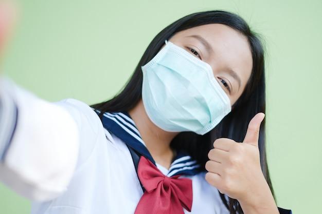 Studentenmeisje draagt een masker en maakt selfie met smartphone