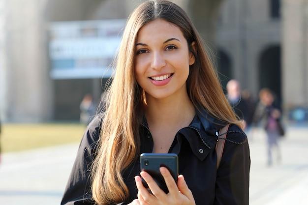 Studentenmeisje het typen op slimme telefoon buiten school bekijkend camera