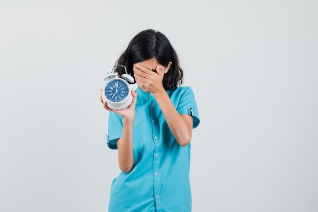 Studentenmeisje in blauw overhemd dat klok toont terwijl gezicht met hand wordt bedekt en bezorgd kijkt